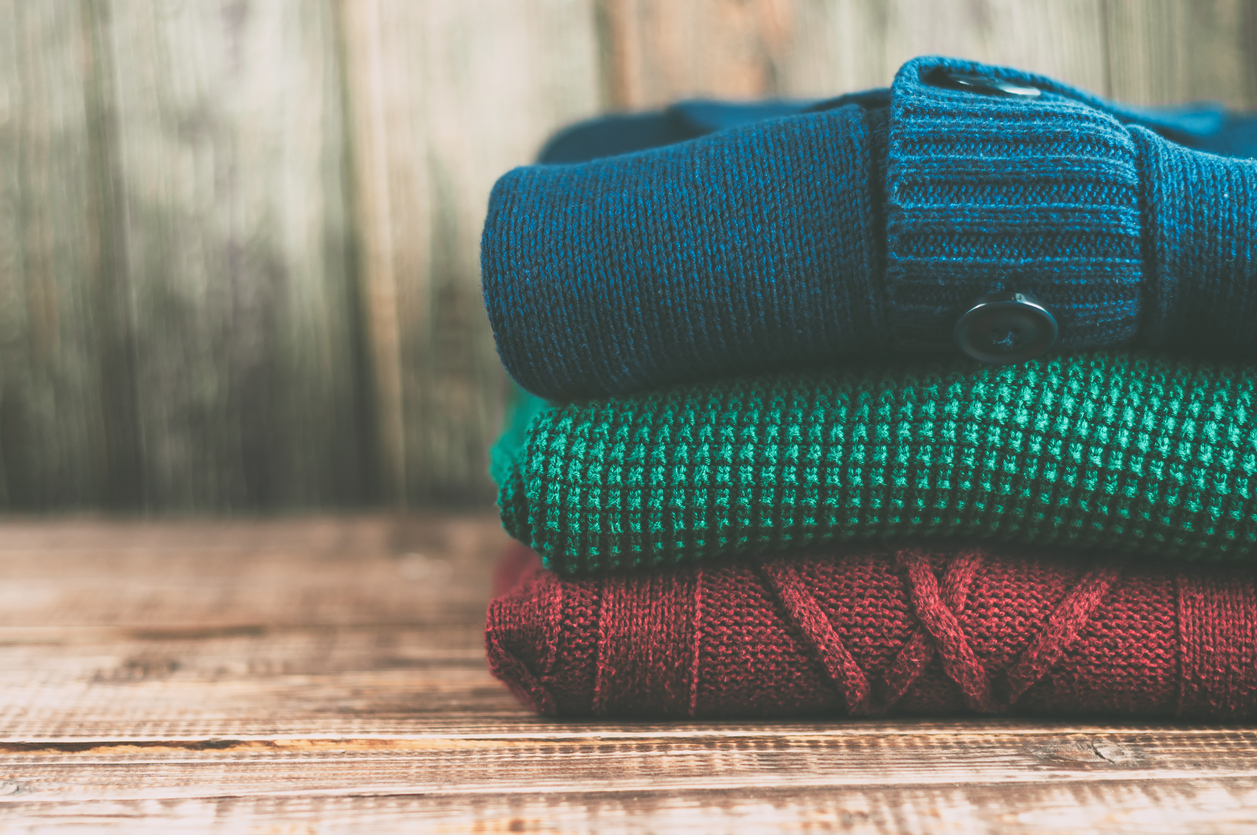 Warm clothes laid in a pile on wooden background.