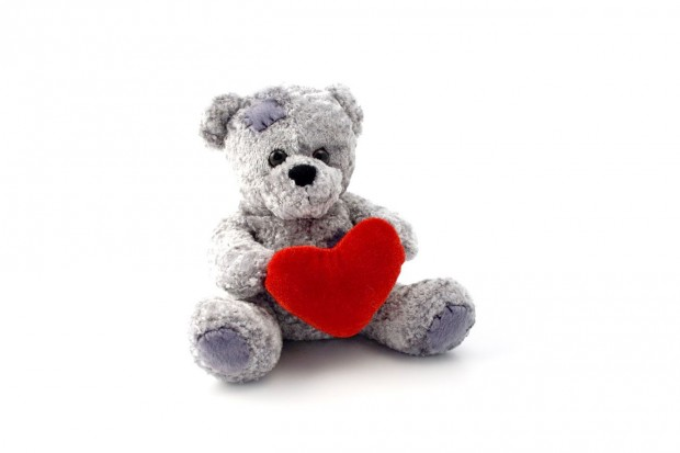 teddy-bear-toy-holding-a-heart-on-white-background