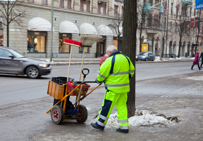 Stockholm, Sweden- March 1, 2011: Trash collector in Stockholm, last of winter snow is melting revealing all the trash.