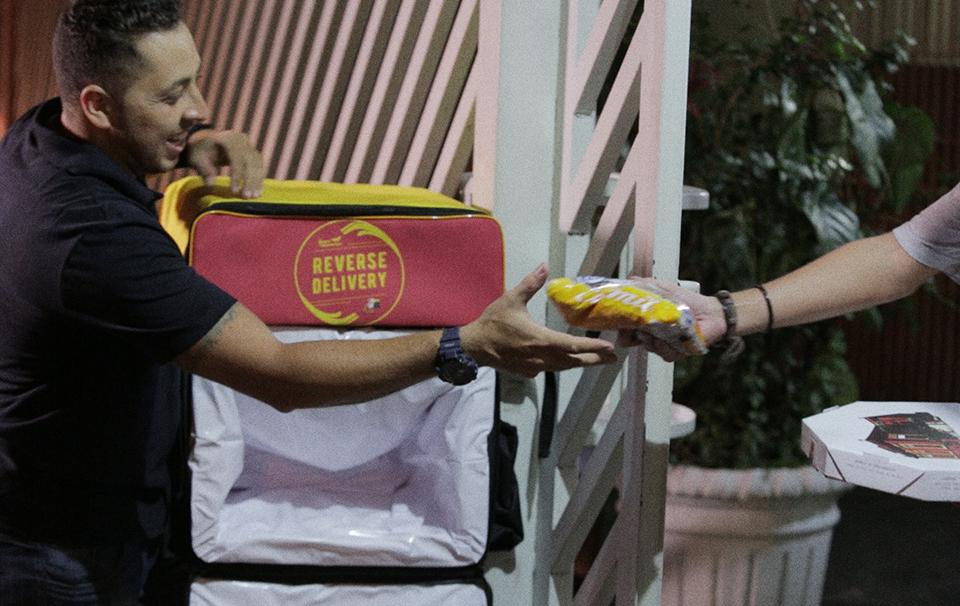 Motoboys entregam pizza e voltam com mochilas carregadas de alimentos para doação