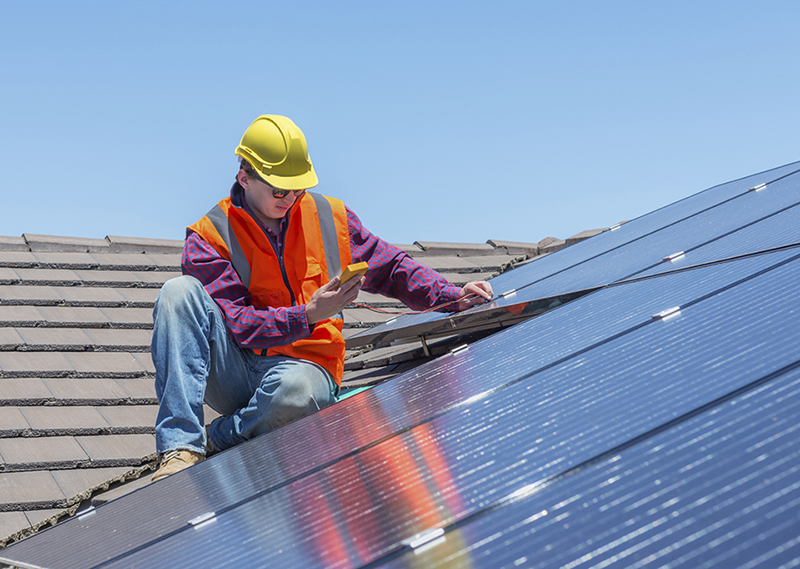 young worker checking solar panels on house roof