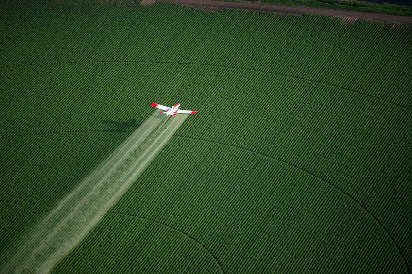 A crop duster working in a farm field