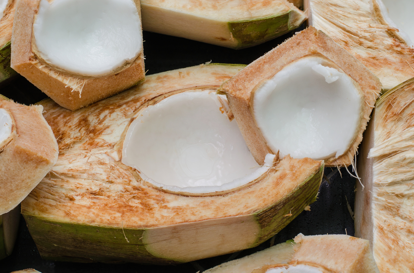Coconut - Tropical green coconut is split into two halves saw the coconut meat inside.