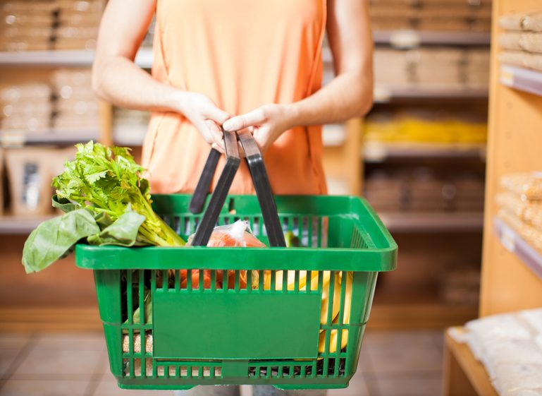 Closeup of a young woman holding a basket full of groceries and organic healthy food in a supermarket