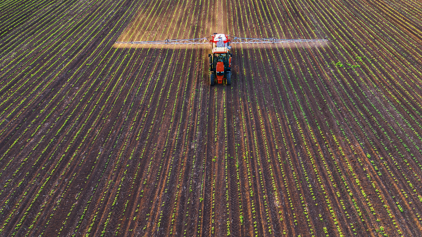 Tractor spraying field at spring,aerial view