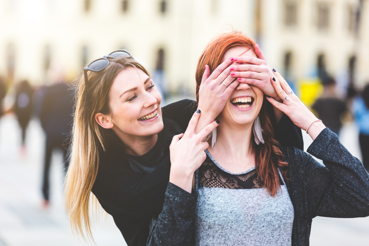 Two young women having fun together. Blonde girl playing peekaboo with her redhead friend. Happiness and lifestyle concepts, candid real people as models