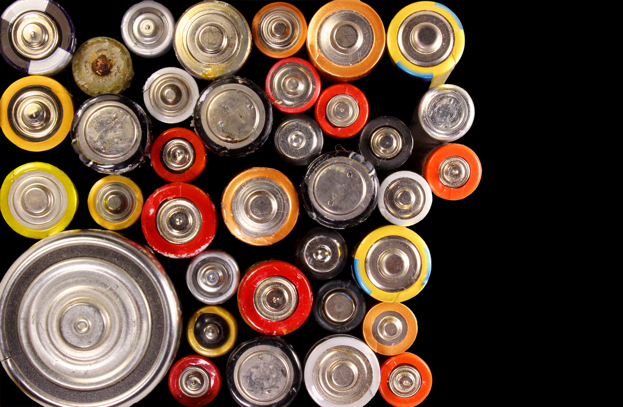 Old electric batteries on black background