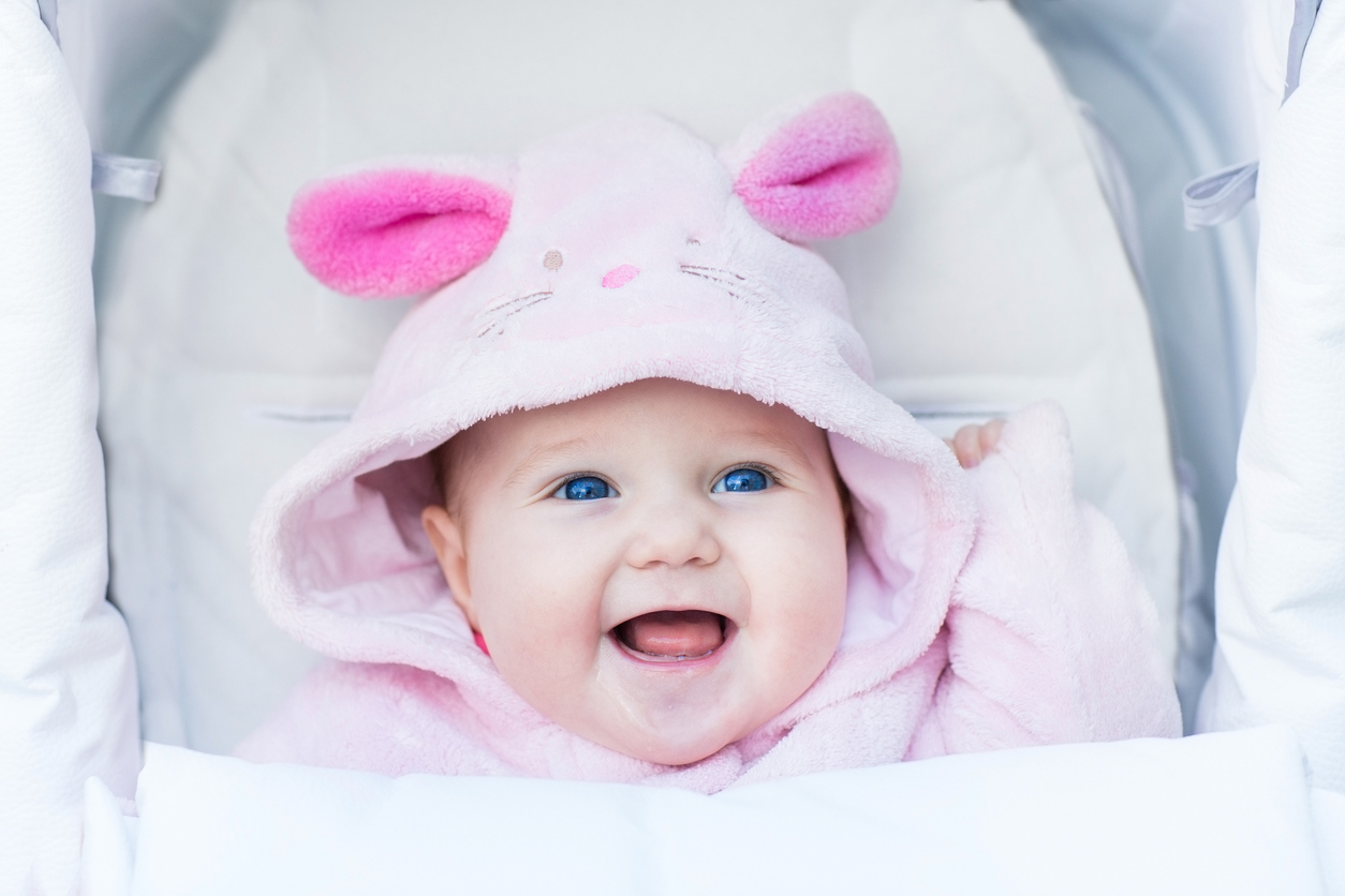 Cute laughing baby girl wearing pink bunny snow suit