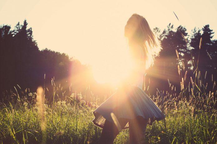 mulher no campo e por do sol